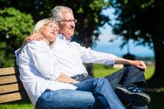 Hög kvinna och man som vilar på att omfamna för bänk Fotografering för Bildbyråer
