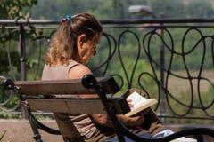 Hög kvinna på balkongsammanträde på bänk och läseboken arkivfoto
