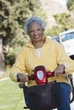 Hög kvinna på den motoriska sparkcykeln Fotografering för Bildbyråer