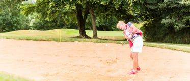 Hög kvinna på golf som har slaglängden i sandbunker Royaltyfri Fotografi