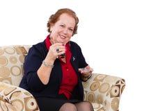 Hög kvinna på hennes Seat som inviterar för att ha ett te Royaltyfri Bild