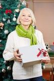 Hög kvinna på jul som rymmer en gåva Arkivfoto
