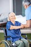 Hög kvinna på rullstolen som hjälps av sjuksköterskan arkivbild