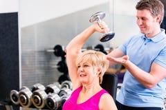 Hög kvinna på sportövningen i idrottshall med instruktören Royaltyfria Bilder
