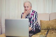 Hög kvinna som är chockad med något på bärbara datorn royaltyfri bild