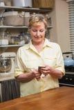 Hög kvinna som överför ett textmeddelande Fotografering för Bildbyråer