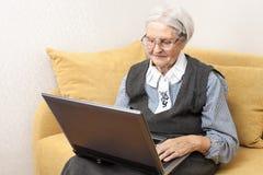Hög kvinna som använder bärbar datordatoren Royaltyfri Bild