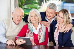 Hög kvinna som använder den Digital minnestavlan med familjen på royaltyfri fotografi