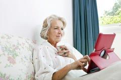 Hög kvinna som använder den digitala minnestavlan, medan ha kaffe på säng hemma Royaltyfria Bilder