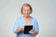 Hög kvinna som använder en trådlös svart minnestavlaPC Royaltyfri Bild