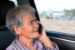 Hög kvinna som använder mobiltelefonen Royaltyfria Bilder