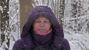 Hög kvinna som applåderar händer i handskar för att skaka snö av i vinterskog arkivfilmer