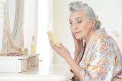 Hög kvinna som applicerar makeup arkivbilder