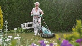Hög kvinna som arbetar i trädgården med gräsklippningsmaskinen royaltyfri fotografi