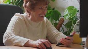 Hög kvinna som arbetar på datoren och att kalla mobilt som skrattar stock video