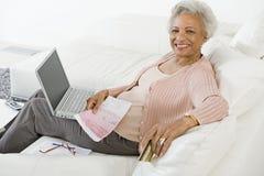 Hög kvinna som betalar räkningar direktanslutet Royaltyfri Fotografi