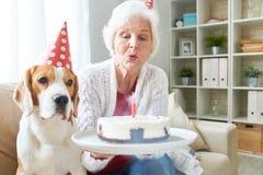 Hög kvinna som blåser födelsedagstearinljus fotografering för bildbyråer