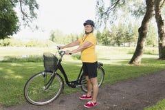 Hög kvinna som cyklar i en parkera på den soliga eftermiddagen Arkivfoto