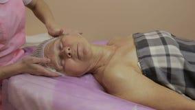 Hög kvinna som får framsidamassage i brunnsortsalong arkivfilmer
