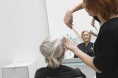 Hög kvinna som får frisyr i salong Royaltyfri Foto