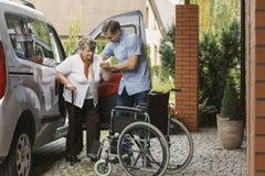 Hög kvinna som får ut ur bilen med hjälpen av en sjuksköterska arkivfoton