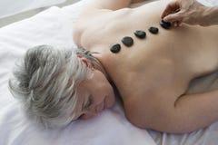 Hög kvinna som får varm stenterapi fotografering för bildbyråer