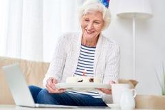 Hög kvinna som firar födelsedag via video pratstund arkivbild
