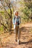 Hög kvinna som fotvandrar skogen Royaltyfri Foto