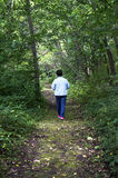 Hög kvinna som går ner en skogbana Arkivfoton