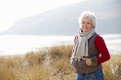 Hög kvinna som går till och med sanddyn på vinterstranden Royaltyfri Foto