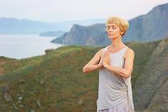 Hög kvinna som gör yogaövningar Arkivbild