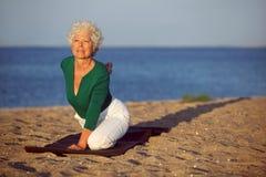 Hög kvinna som gör yoga vid havet royaltyfria bilder