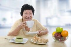 Hög kvinna som har frukosten Arkivbild