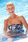 Hög kvinna som har gyckel i simbassäng Arkivbilder