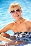 Hög kvinna som har gyckel i simbassäng Arkivfoto