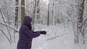 Hög kvinna som har gyckel, upp väljer snö från jord och kastar den i luften stock video