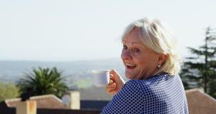 Hög kvinna som har kaffe i balkongen 4k arkivfilmer