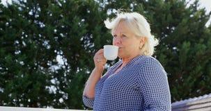 Hög kvinna som har kaffe på terrassen 4k lager videofilmer