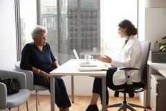 Hög kvinna som har konsultation med kvinnlig doktor In Hospital Office arkivbild