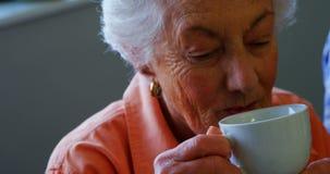 Hög kvinna som har kopp te på avgånghemmet 4k arkivfilmer