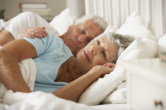 Hög kvinna som har svårighet, i att sova i säng med maken Fotografering för Bildbyråer