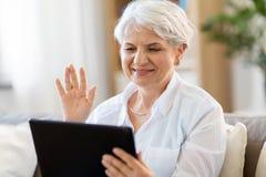Hög kvinna som har video pratstund på minnestavlaPC royaltyfria bilder