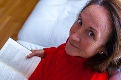Hög kvinna som hemma läser en bok Royaltyfria Foton