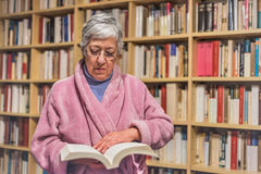Hög kvinna som hemma läser en bok koncentrerat uttryck A arkivbilder