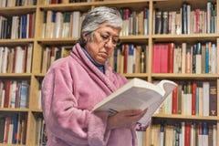 Hög kvinna som hemma läser en bok koncentrerat uttryck A fotografering för bildbyråer