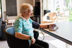 Hög kvinna som hemma mäter blodtryck fotografering för bildbyråer
