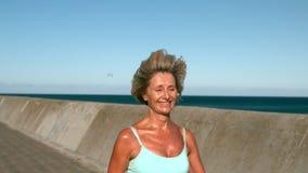 Hög kvinna som joggar på en solig dag arkivfilmer
