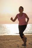 Hög kvinna som joggar på havsstranden Royaltyfri Fotografi