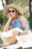 Hög kvinna som kopplar av i sommarträdgård Royaltyfri Foto