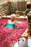 Hög kvinna som kopplar av i täckt pöl för blomma kronblad på Spa Royaltyfria Foton